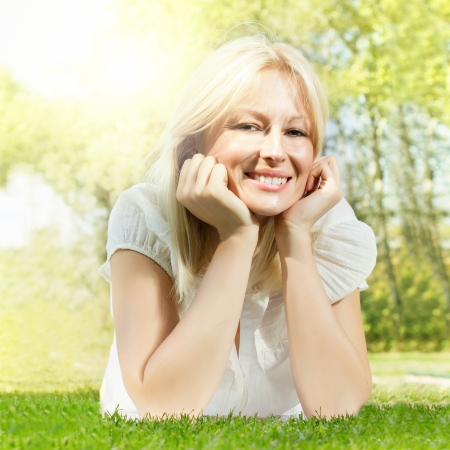Happiness smiling blonde woman relaxing on green grass in the park. photo