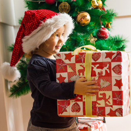 Cute little girl with Santa hat holding a Christmas gift at home. photo