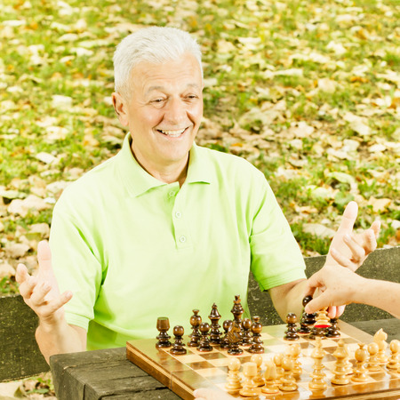Happy senior man playing chess on a park bench. photo