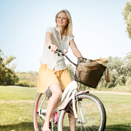 Happy smiling young woman with a bicycle in the park. photo
