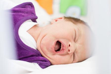 Portrait of crying newborn baby girl. photo