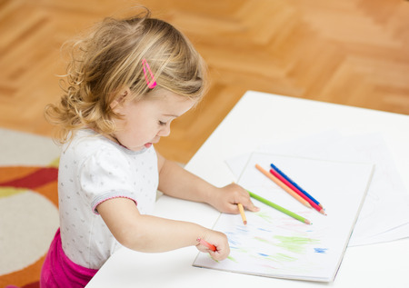 childcare: Little girl drawing with colorful crayons at home.