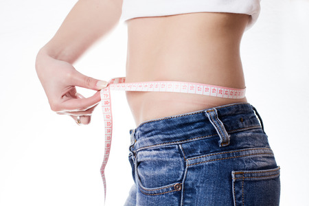 woman measuring: Young woman in jeans measuring waist with tape. Stock Photo