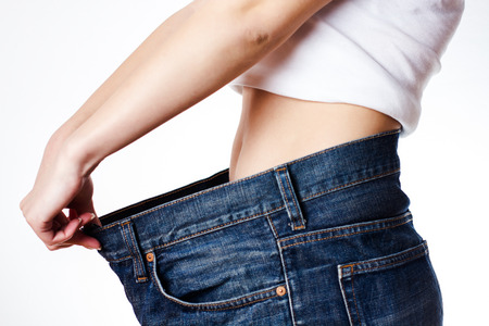 Slim waist of young woman in big jeans showing successful weight loss. photo