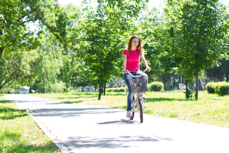 Young woman riding a bike in the park. photo