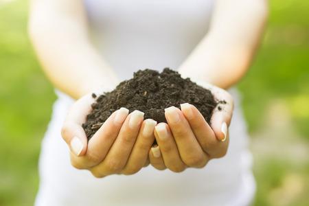 origins: Human hands holding a handful of soil.