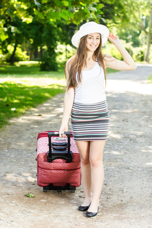 Attractive young woman with a suitcase ready for travel. Stock Photo - 29545437
