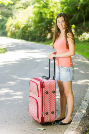 Attractive young woman with a suitcase ready for travel. Stock Photo - 29545443