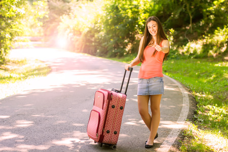 Attractive young woman with a suitcase ready for travel. Stock Photo - 29545188