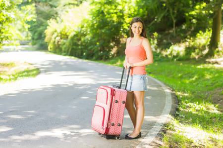 Attractive young woman with a suitcase ready for travel. Stock Photo - 29545189