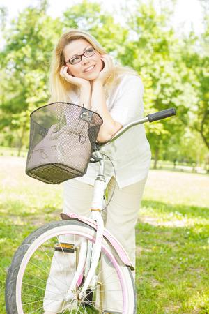 enjoying life: Happy young woman on the bike enjoying nature. Stock Photo