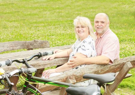 Happy elderly couple relaxing in the park after ride bike. photo
