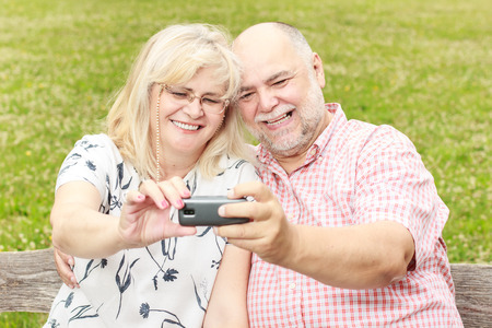 Happy senior couple taking selfie in the park. photo
