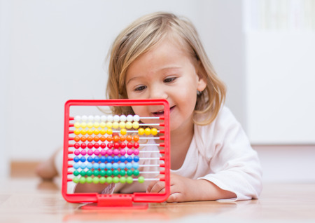 Little girl learning with abacus lying on floor. photo
