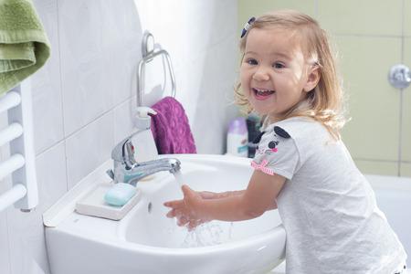 Little girl washing her hands in bathroom. Archivio Fotografico
