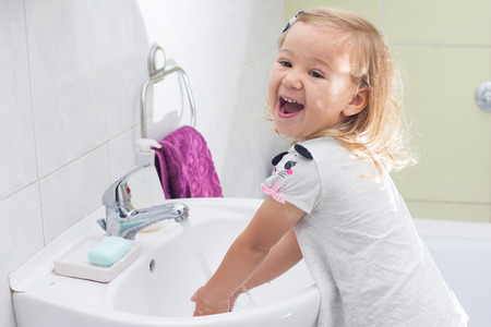 Little girl washing her hands in bathroom. Stock Photo