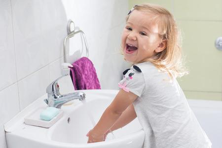 lavandose las manos: Niña lavar sus manos en el baño.