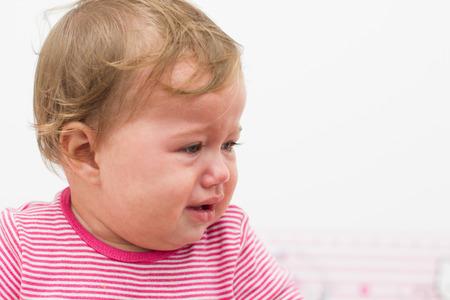 baby huilen: Portret van huilende baby van negen maanden meisje. Stockfoto