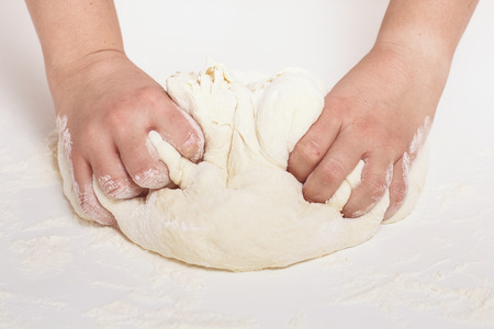 kneading: Woman Hands Kneading Dough on the table.