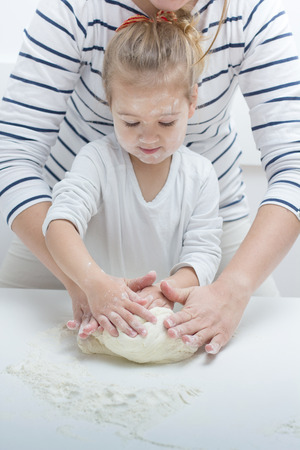 life support: Cute little girl with her mother kneading dough at home. Stock Photo