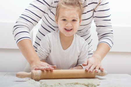 little dough: Cute little girl with her mother kneading dough at home. Stock Photo