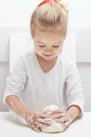 kneading: Happy little girl have fun with kneading dough at home.
