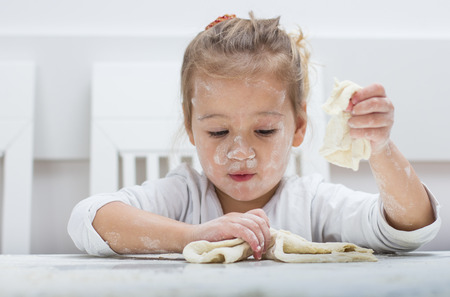 little dough: Happy little girl have fun with kneading dough at home.