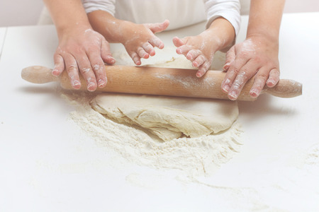 knead: Mother and Daughter Hands Kneading Dough on the table. Stock Photo
