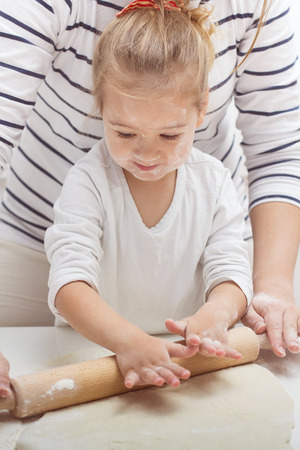 kneading: Cute little girl with her mother kneading dough at home. Stock Photo