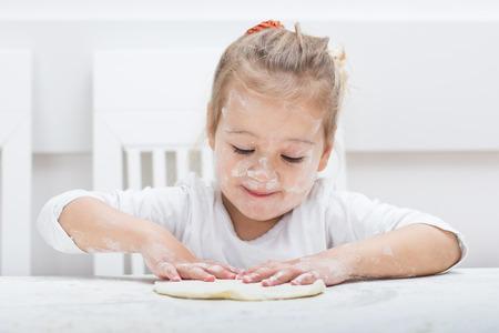haciendo pan: Niña feliz se divierte con amasando en casa.