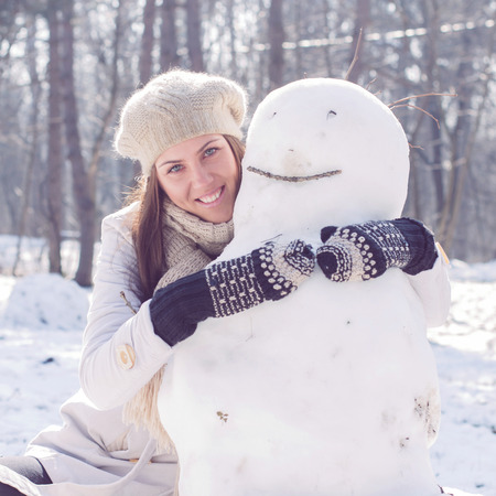 Winter Happy Woman Embracing Snowman in the park. Caucasian female wintertime outdoor. photo