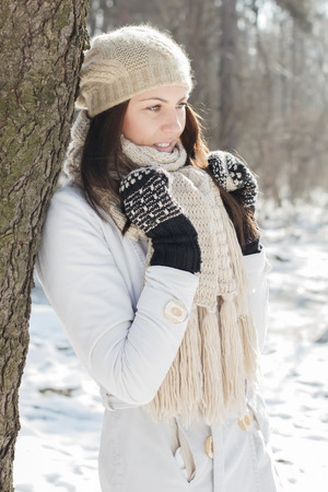 Smiling Lovely Young Woman Winter Portrait at beautiful sunny winter day in the park. Happy Caucasian female wintertime season outdoor. photo