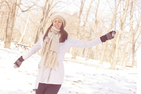 Enjoyment Happy Lovely Relaxing Young Woman Enjoying Winter. Portrait at beautiful sunny winter day in the park. Caucasian carefree female with spreading hands wintertime season outdoor. photo