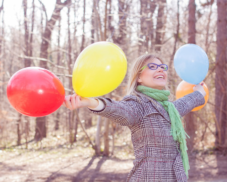Happy Young Caucasian Woman holding colorful balloons at beautiful sunny day in nature.Winter autumn season outdoor. photo