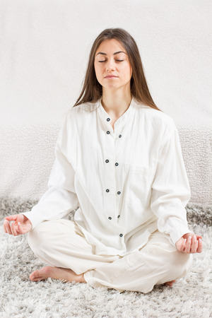 Young Woman Doing Yoga Meditation at home. Caucasian female relaxing .  Healthy Lifestyle. photo