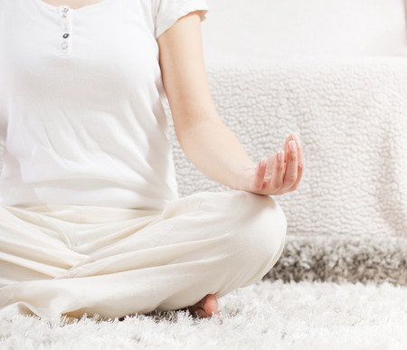 Yoga Meditation Woman Relaxing at home.Healthy Lifestyle in Lotus Posture .Unrecognizable caucasian female meditate  on the floor. photo