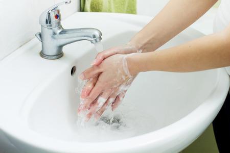 de higiene: Lavarse las manos con agua que fluye en el baño. Higiene
