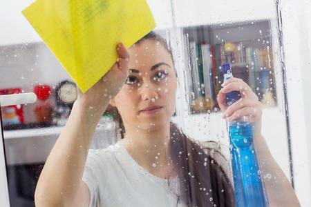 maid: Joven mujer de limpieza de Windows de cristal en la casa.