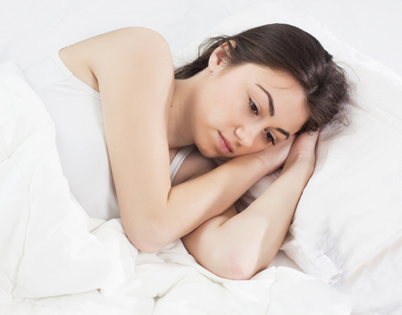 anxious: Worried Young Woman with Insomna laying in the bed. Stock Photo