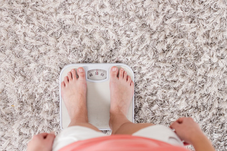 Female standing on scale for measuring. Unrecognizable person. Weight loss concept at home. View from above.