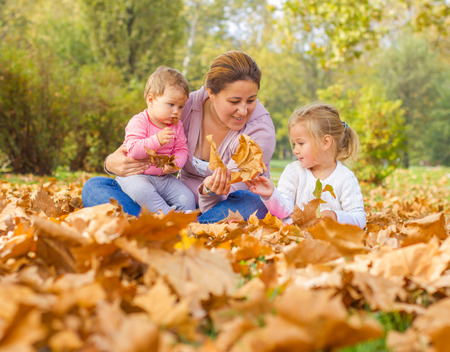 Happy Family Enjoyment Beautiful Autumn Day Mother with two Daughters in the park. Happiness Family carefree Relaxing fall season concept.