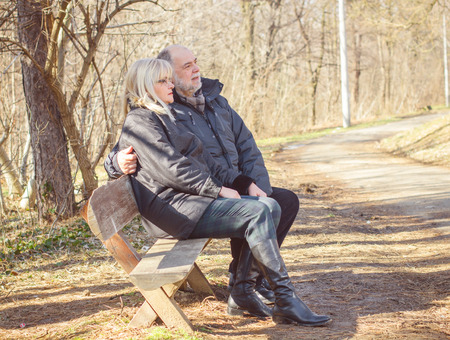 people sitting: Happy Elderly Senior Couple Relaxing in the nature. Old people sitting on the bench portrait outdoor winter autumn season.