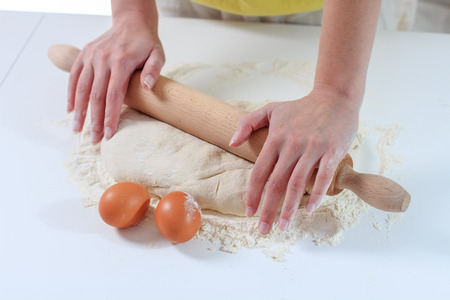 preparing food: Female Hands Rolling Dough with Rollingpin for baking .Homemade Preparing Food.