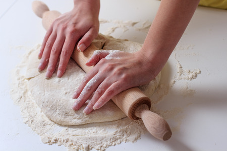 culinary skills: Female Hands Rolling Dough with Rollingpin for baking .Homemade Preparing Food.