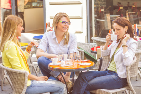 day break: Three Young Women have Coffee Break Together in street cafe. Caucasian female relaxing on beautiful summer day in the city. Stock Photo