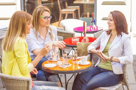 socializando: Tres mujeres jóvenes tienen Coffee Break Juntos en café de la calle. Mujeres de raza caucásica relajante en el hermoso día de verano en la ciudad.