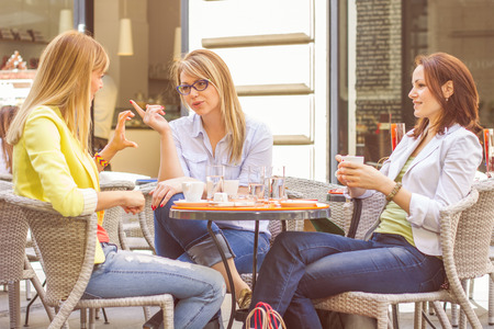 Three Young Women have Coffee Break Together in street cafe. Caucasian female relaxing on beautiful summer day in the city. Stockfoto