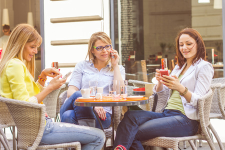 Three Young Women have Coffee Break Together in street cafe. Caucasian female using mobile phone. Standard-Bild