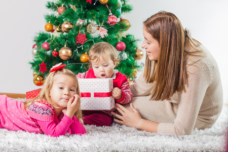 baby open present: Christmas Happy Family mother and her two little daughters sitting on the floor and open Holidays Gift. Stock Photo