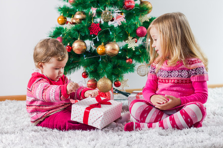christmas presents: Happy children open Christmas presents on the floor and tree with New Year decoration at home.